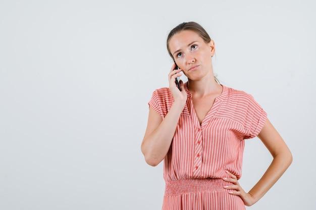 Молодая женщина разговаривает по мобильному телефону с рукой на талии в полосатом платье и смотрит задумчиво, вид спереди.