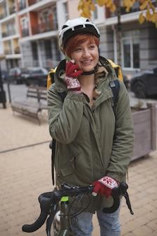 Молодая женщина разговаривает по своему смартфону, работая курьером по доставке