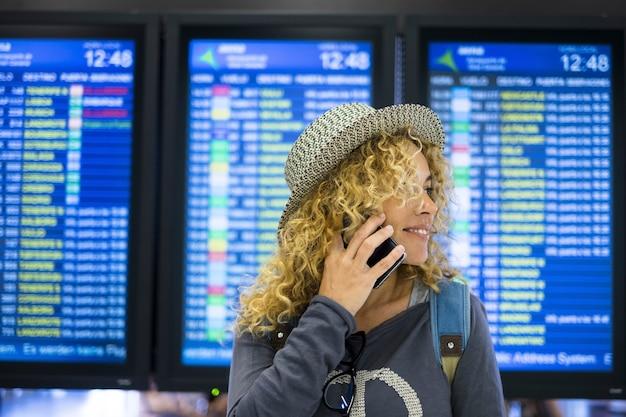 旅行中に空港で携帯電話で話している若い女性。空港のデジタルディスプレイの前で目をそらし、携帯電話で話している帽子をかぶった女性の乗客