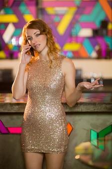 Молодая женщина разговаривает по мобильному телефону на стойке