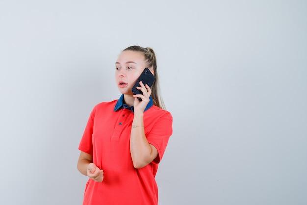 Tシャツを着て携帯電話で話し、物思いにふける若い女性