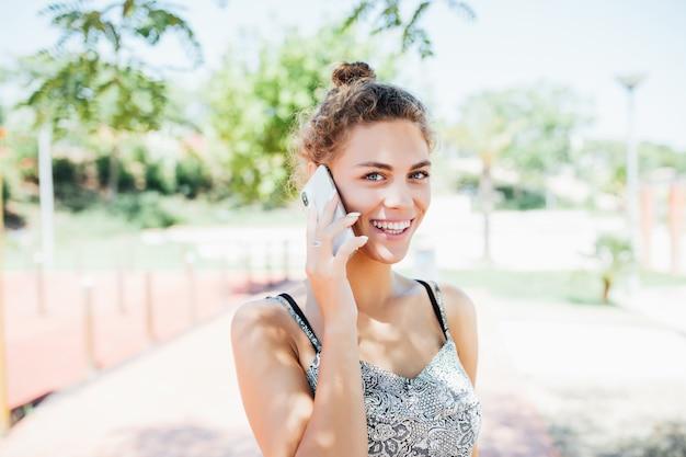 通りで携帯電話で話している若い女性