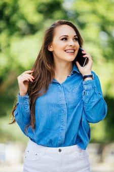 Молодая женщина разговаривает по мобильному телефону на летней улице