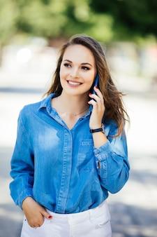 夏の街で携帯電話で話している若い女性