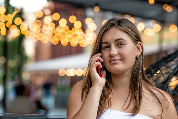 가벼운 bokeh 배경으로 거리 밤에 휴대 전화에 말하는 젊은 여자