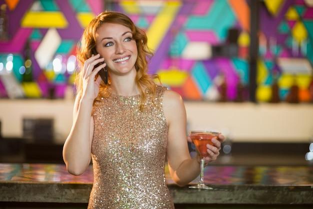 Молодая женщина разговаривает по мобильному телефону, имея коктейль у прилавка