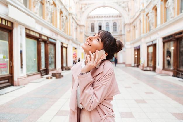 通りに立っている間携帯電話で話している若い女性