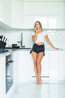 Молодая женщина разговаривает по мобильному телефону при использовании ноутбука на кухне у себя дома