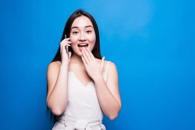 スマートフォンで話し、青い壁に孤立した驚きを表現する若い女性
