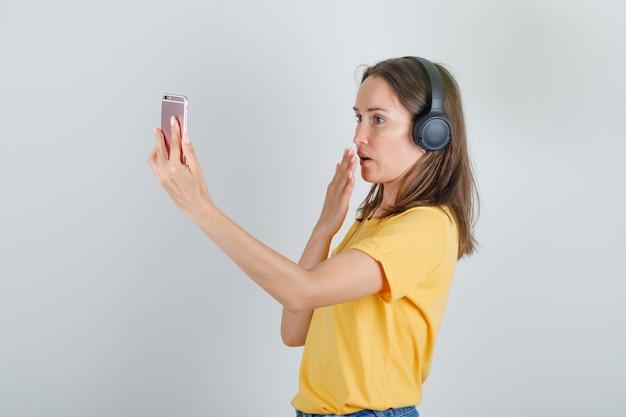 黄色のtシャツでビデオ通話を介してスマートフォンで話している若い女性