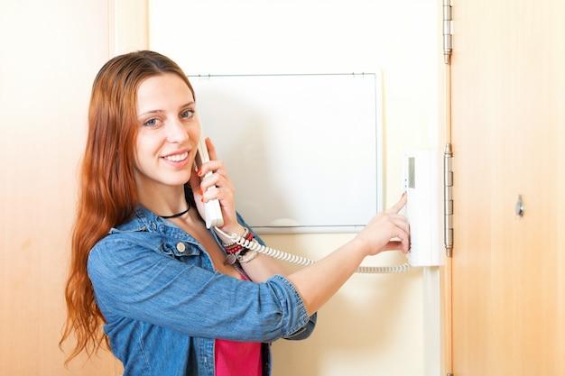Молодая женщина разговаривает по дому видеофон в помещении
