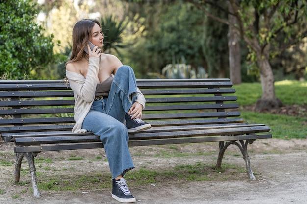 공원에 앉아 휴대전화로 통화하는 젊은 여성
