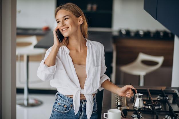 電話で話し、朝のコーヒーを作る若い女性