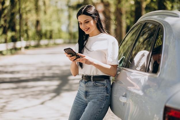그녀의 전기 자동차로 전화 통화하는 젊은 여자