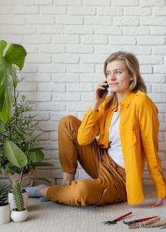 彼女の工場の隣で電話で話している若い女性