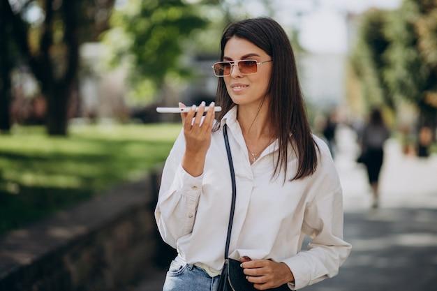 거리 밖에서 전화 통화를 하는 젊은 여성
