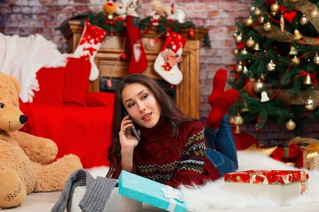 Молодая женщина разговаривает по телефону самоизоляции на фоне рождественских украшений