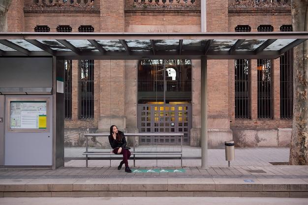 젊은 여자는 버스를 기다리고 전화 통화
