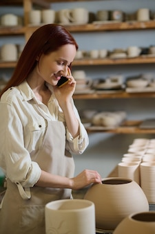 Молодая женщина разговаривает по телефону, стоя в гончарной мастерской