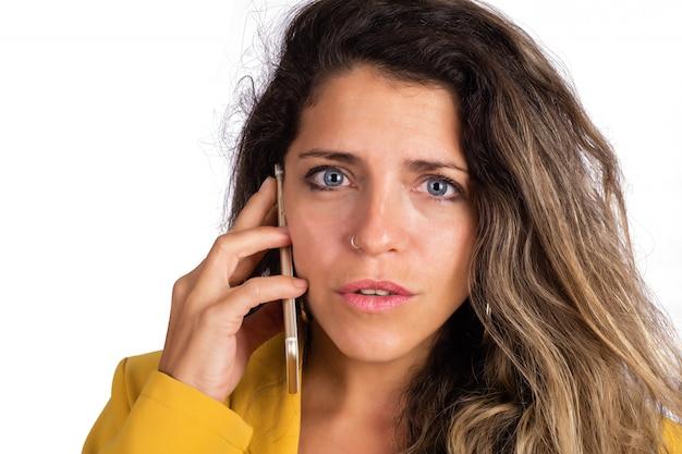 Молодая женщина разговаривает по телефону.