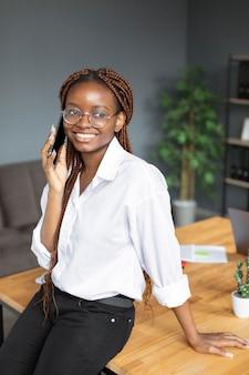 Молодая женщина разговаривает по смартфону на работе