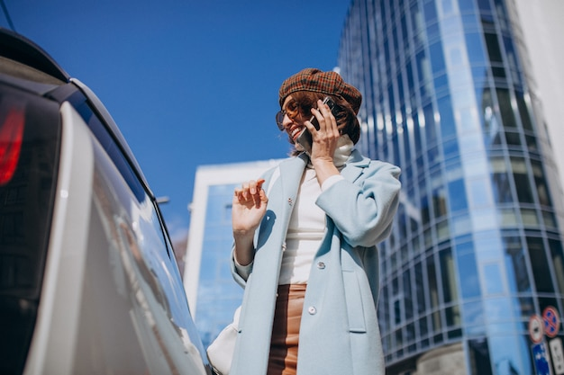 Young woman talking on the phone by electro car in the center