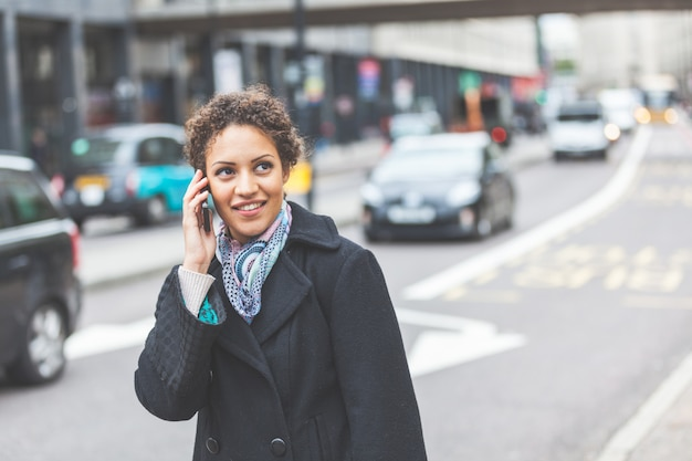 Young woman talking on the phone in london.