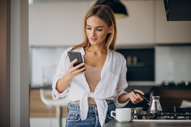 Young woman talking on the phone and making morning coffee