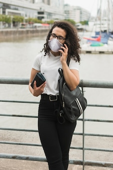 Giovane donna che parla al telefono all'aperto