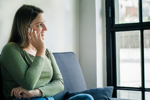 Young woman talking on phone on sofa