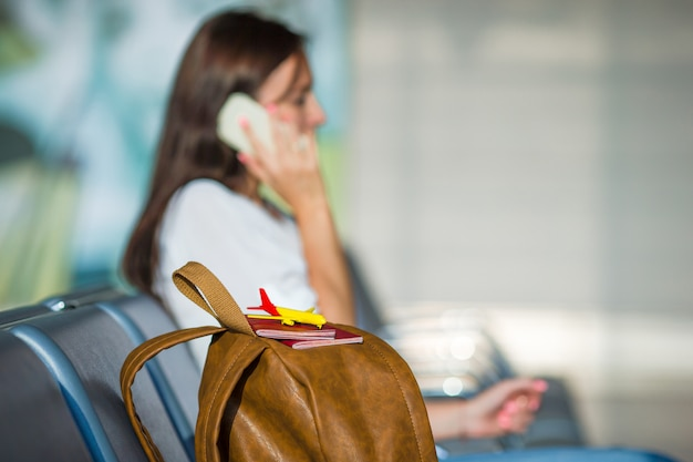 Young woman talking on the phone while waiting boarding