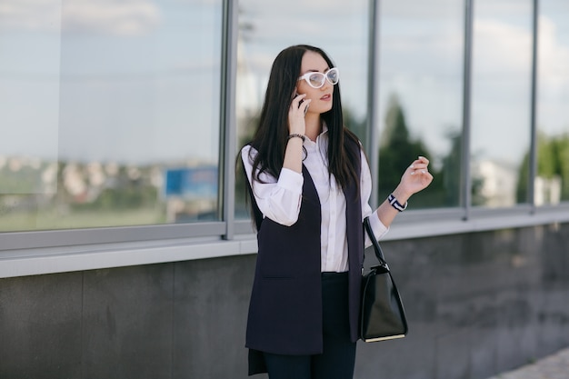 Young woman talking on a phone with a black bag