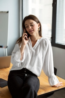 Young woman talking on the smartphone at work
