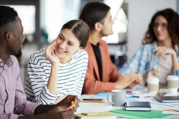 会議で同僚と話している若い女性