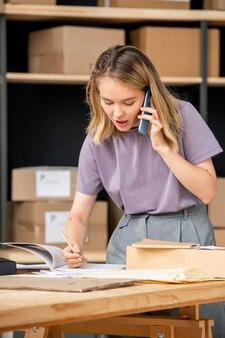 Молодая женщина разговаривает с одним из клиентов по телефону в кладовой, проверяя информацию о заказе перед его упаковкой и отправкой