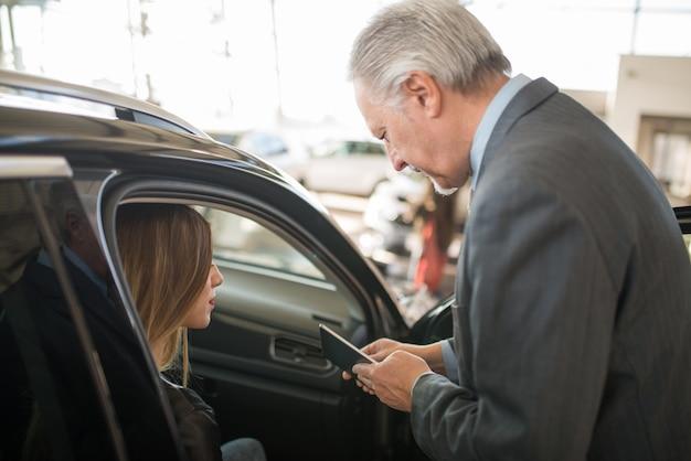 쇼룸에서 새 차를 사기 위해 판매원과 이야기하는 젊은 여성