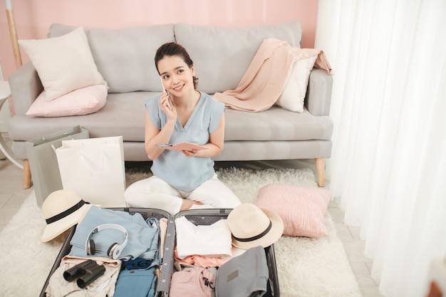 夏休み旅行やワンダーラストのコンセプトで服や物事を整理するパスポートパッキング旅行スーツケースを持って携帯電話で友人と話している若い女性