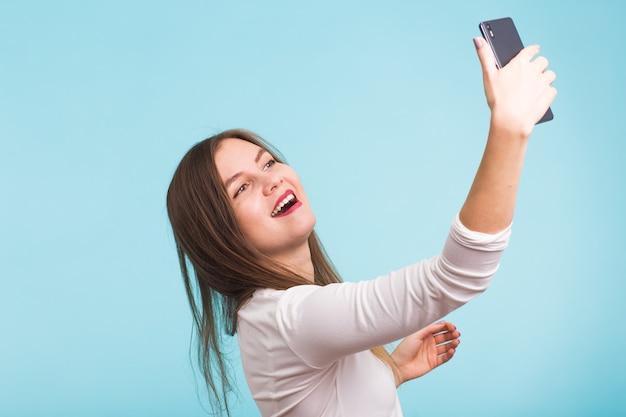 스마트 폰 화상 통화를 통해 친구와 이야기하는 젊은 여자. 비디오를 갖는 아름 다운 소녀