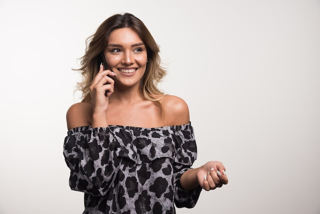 白い壁に楽しく電話で話している若い女性。