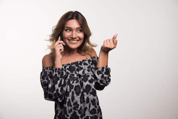 Молодая женщина счастливо разговаривает с телефоном на белой стене.