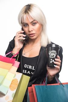 흰색 바탕에 쇼핑백과 컵을 들고 전화로 얘기하는 젊은 여자. 고품질 사진