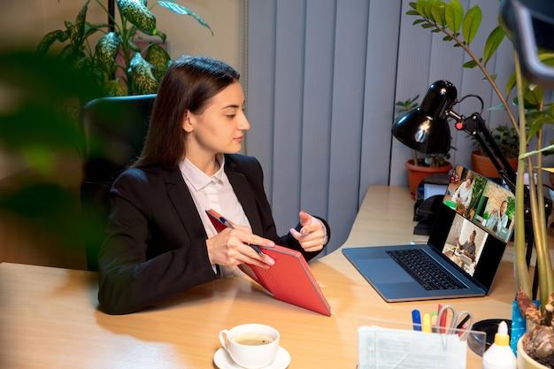 ホームオフィスで同僚とビデオ会議中に働いて話している若い女性