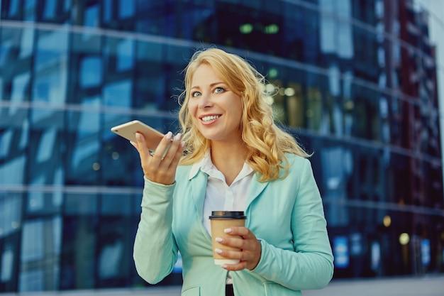 젊은 여성이 휴대폰으로 이야기하고 밖에서 커피를 마신다