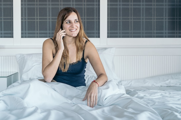 Young woman talks on the phone when she wakes up in her bed
