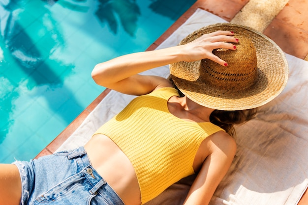Young woman tanning poolside