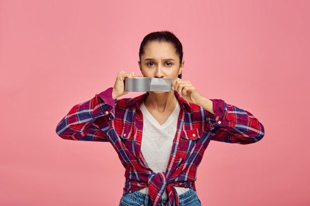 Молодая женщина заклеила рот скотчем, розовая стена, эмоции. выражение лица, лицо женского пола, смотрящее на камеру в студии, эмоциональная концепция, чувства