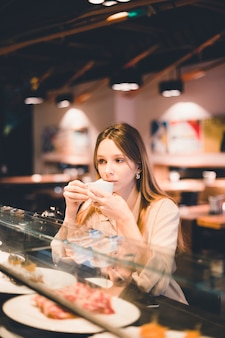 Young woman tasting coffee
