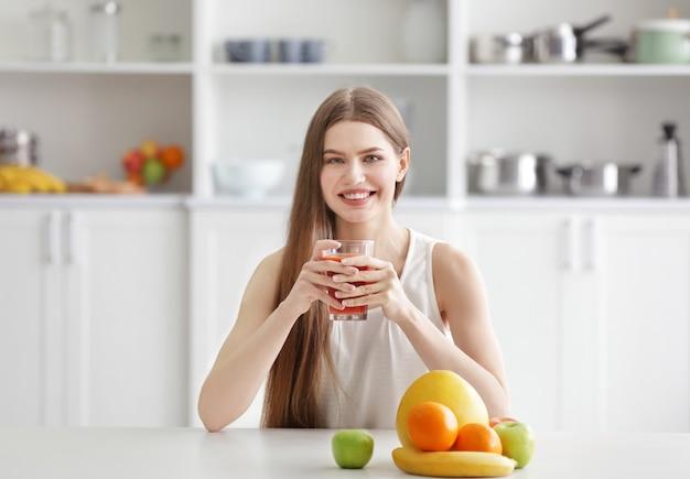 Молодая женщина, дегустация свежего сока на кухне