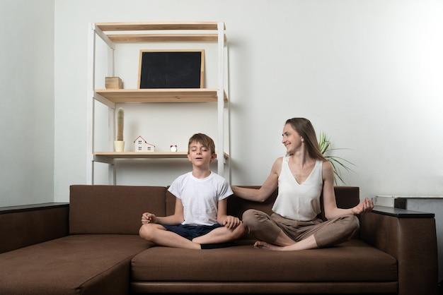 Молодая женщина обучает мальчика медитации, сидя на диване. йога дома с детьми.