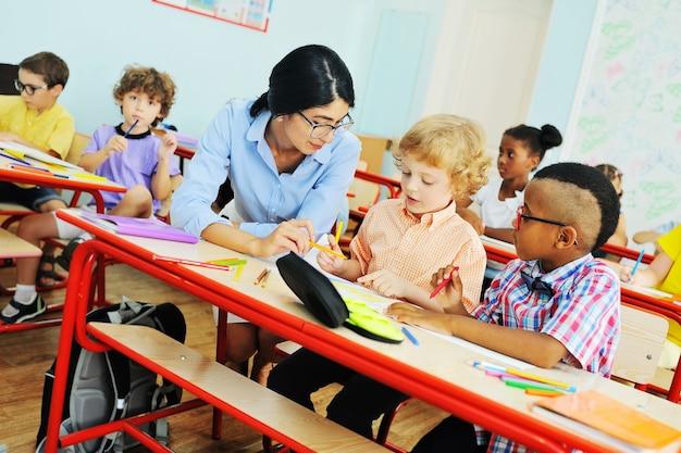 Молодая учительница помогает детям выполнять работу в классе в начальной школе